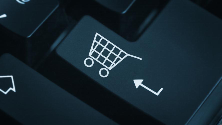Foco em tecla de um teclado preto de computador. Nela, há um desenho de carrinho de compras e uma seta.